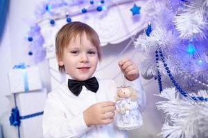 boy in shirt and bow tie decorates a Christmas tr