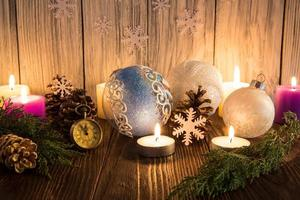 Christmas tree decorations and candles on an old wooden backgrou photo