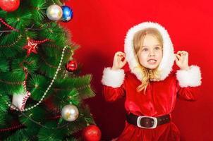 kleines Mädchen in der Nähe des Weihnachtsbaumes