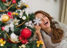 mujer feliz sentada jugando con la decoración del árbol de navidad