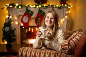 woman sitting at fireplace with cup of tea at Christmas
