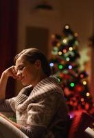 träumende junge Frau, die im Sessel nahe Weihnachtsbaum sitzt