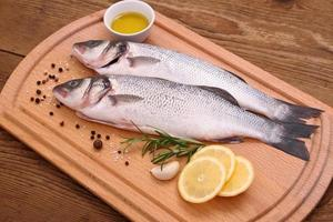 Two fresh sea bass fish on cutting board