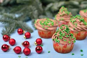 cupcakes com creme de chocolate em um fundo azul de madeira