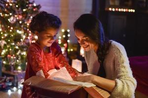 época de natal, mãe e filha abrindo um presente perto da árvore