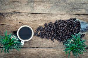 taza de café y granos de café en el escritorio, vista superior foto