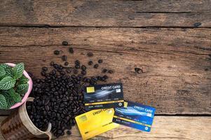 tarjetas de crédito y granos de café en el escritorio, vista superior foto