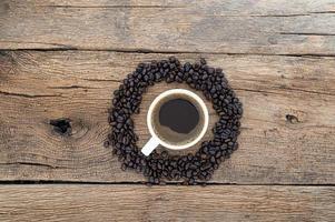 taza de café y granos de café en el escritorio
