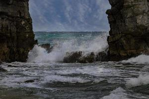 Waves crashing between to pillars of rock