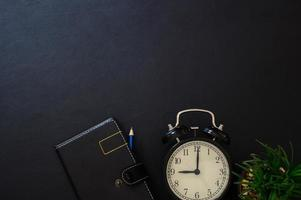 Notebook and clock on the desk, top view