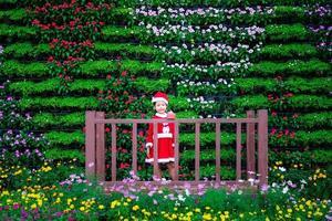 niña asiática en traje rojo de santa claus