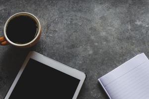 taza de café y tableta en la mesa