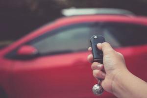 Hombre presionando el botón en la llave del coche de control remoto