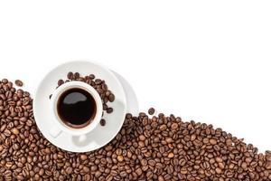 Taza de café expreso y granos tostados sobre fondo blanco.