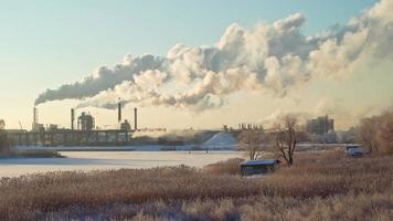 fumaça de fábrica de compensado subindo durante um dia frio de inverno