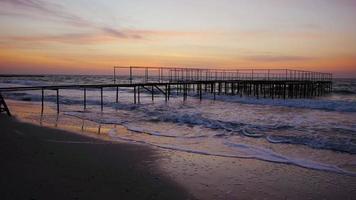 zonsopgang weerspiegeld op nat zandstrand zand met inkomende oceaangolven en pier op een achtergrond