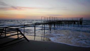 prachtige zonsopgang weerspiegeld op nat zandstrand met inkomende oceaangolven en pier op een achtergrond