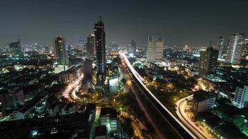 foto com lapso de tempo da vida noturna na cidade grande, arranha-céu iluminado, trânsito, interseção, bangkok, Tailândia