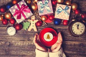 Female holding cup of coffee near christmas gifts