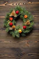 Christmas wreath on brown wooden table top view