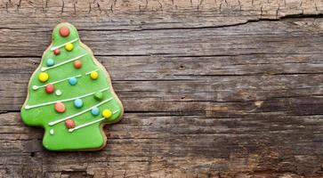 Galletas de jengibre caseras de Navidad en mesa de madera foto