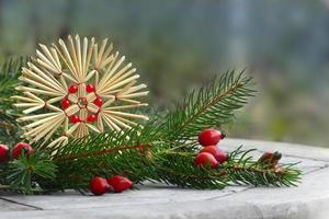 christmas decoration, straw star, rose hips and pine branch photo