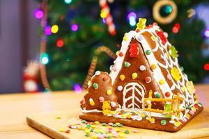 maison en pain d'épice avec arbre de Noël et lumières sur fond.