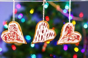 Galletas de jengibre colgando con árbol de Navidad en el fondo.