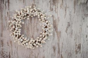 Corona decorativa de Navidad blanca sobre fondo de madera foto