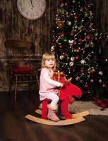 little girl on a toy horse photo