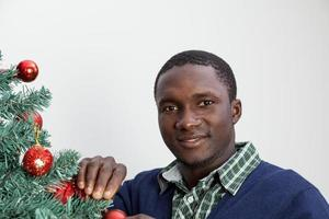 Man decorating the Christmas tree and looking at camera photo