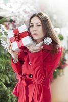 Mujer joven muestra sus paquetes de regalo dentro de una tienda de Navidad