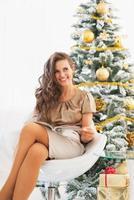 Sonriente joven leyendo una revista cerca del árbol de navidad