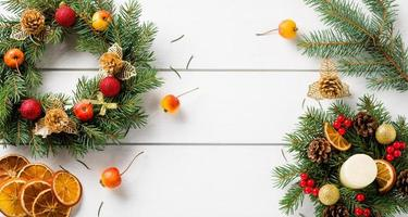 Christmas wreath on white wooden table top view