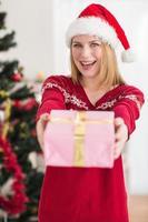 sonriente mujer festiva ofreciendo un regalo rosa foto