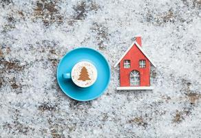 Cappuccino with christmas tree shape and toy home on artificial