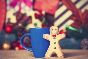 Hombre de pan de jengibre cerca de la taza y regalos de Navidad en el fondo.