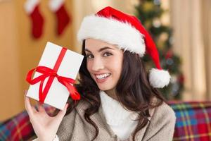 Festive brunette showing gift at christmas