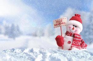 Snowman with a placard Feliz Navidad on the snow photo