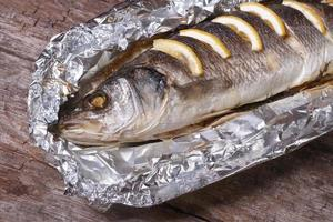 Sea bass with lemon baked in foil. closeup