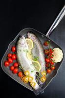 raw fish with vegetables in pan