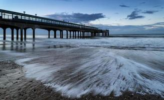 Dawn landscape of pier stretching out into sea photo