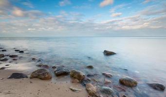Beautiful long exposure landscape of rocky sea shore photo