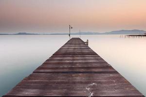 Wood bridge in sea at sunrise photo