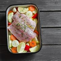 Cooking healthy food - baked fish with vegetables photo