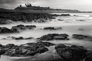 Castillo de Dunstanburgh, piscinas de rocas y mar del norte - larga exposición foto