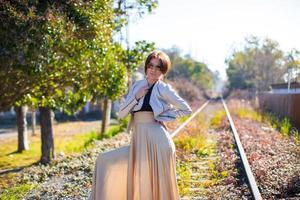 Charming young woman in a long beautiful dress photo