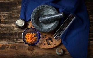 cáscara de naranja, bayas de enebro, sal marina y mortero de granito foto