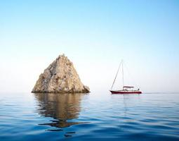 sailing yacht next to a rock in the sea photo