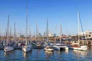 Sailing yachts and pleasure boats are moored in Barcelona port